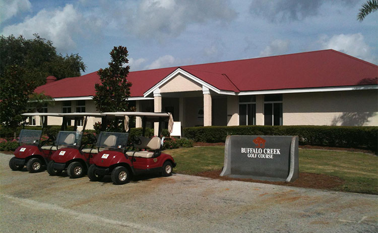 A fleet of golf carts sits in front of the clubhouse at Buffalo Creek